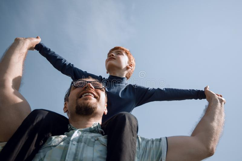 Happy father has a little son on his shoulders stock images