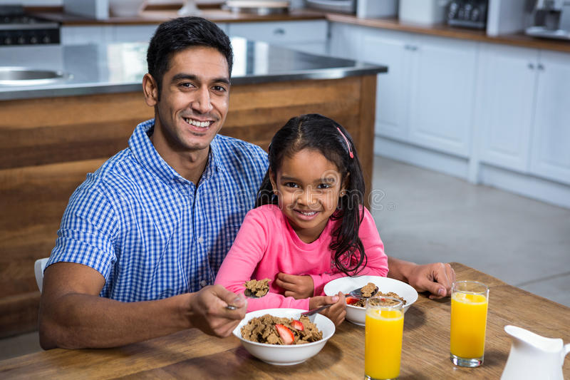 Happy father having breakfast with his daughter royalty free stock photography