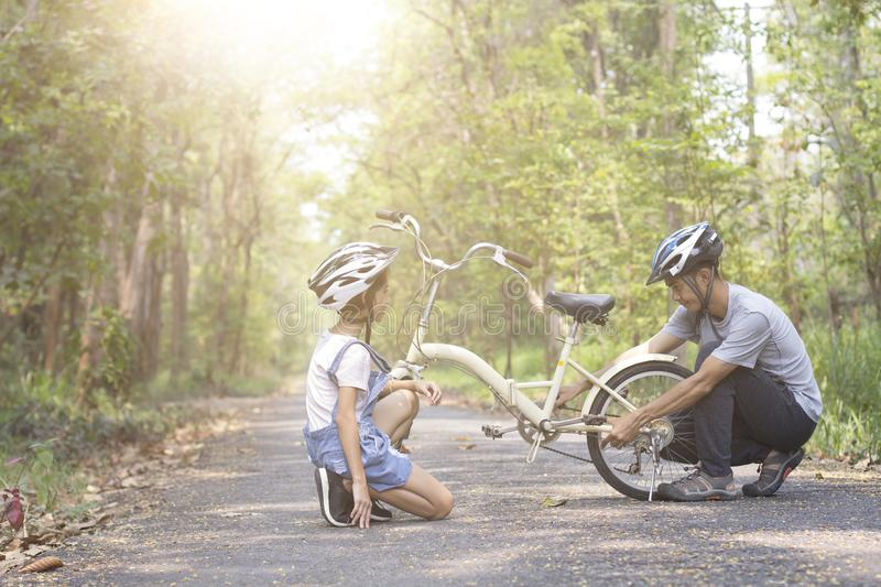 Happy father helped his daughter repair the bike stock photos