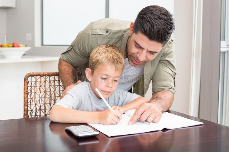 Happy father helping son with math homework at table. At home in kitchen stock photography