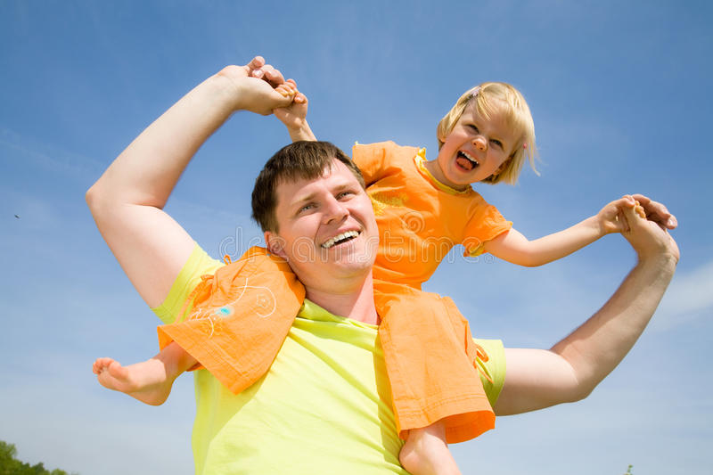 Happy father with his little daughter. Happy father has a good summer time with his little daughter background on the blue sky royalty free stock images