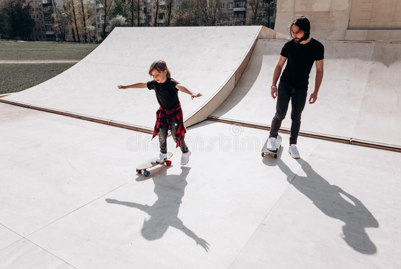 Happy father and his little son dressed in the casual clothes ride skateboards in a skate park with slides at the sunny stock image