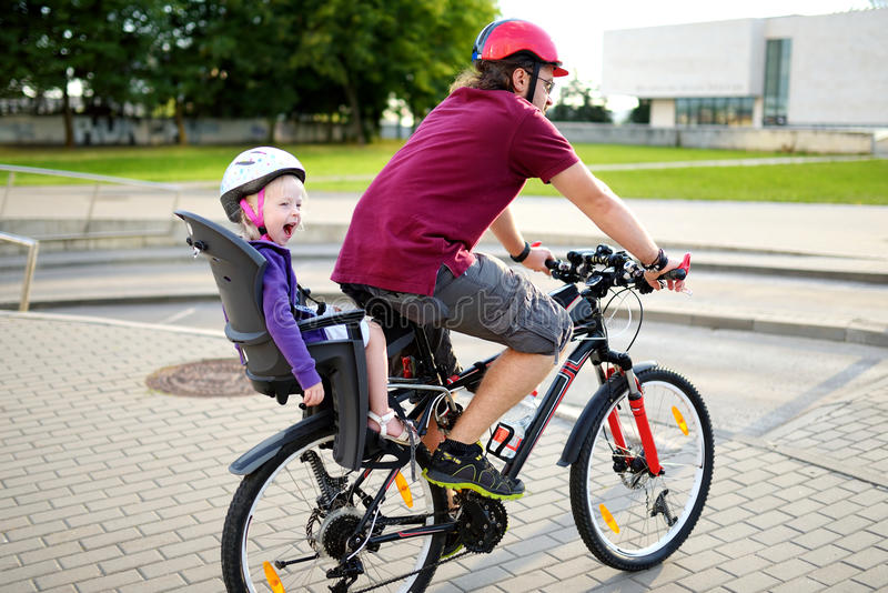 Happy father and his little toddler daughter rinid a bike together stock photos