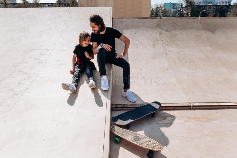 Happy father and his son dressed in the casual clothes are sitting and laughing at the slide in a skate park next to the royalty free stock images