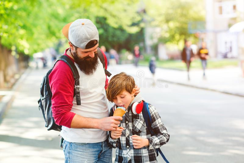 Happy father and his son having fun on a walk. Boy eating ice cream. Family, fatherhood and parenthood stock image