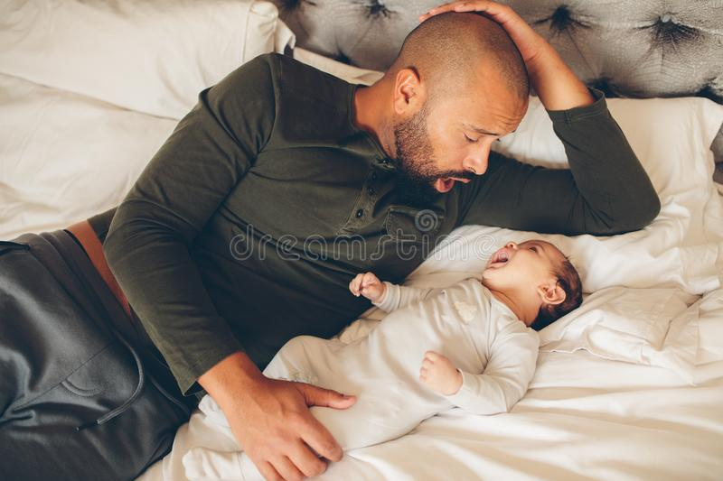 Happy father with his son playing on the bed royalty free stock photography