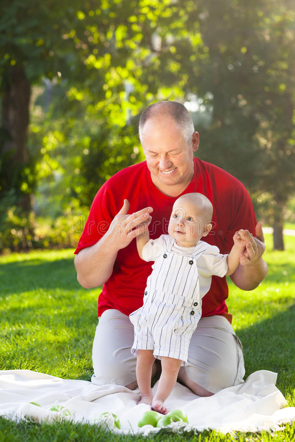 Happy father and his son playing in park together. Outdoor portrait of happy family royalty free stock photo