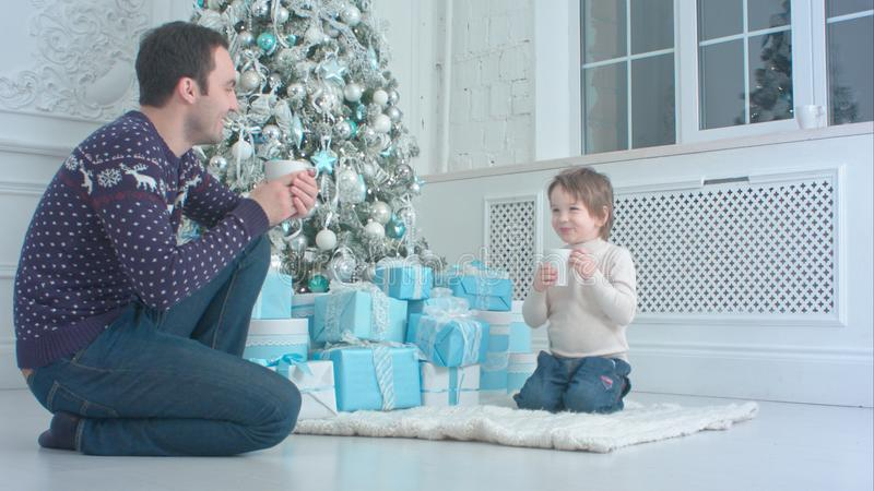 Happy father with his son sitting near the Christmas tree and drinking hot tea royalty free stock image