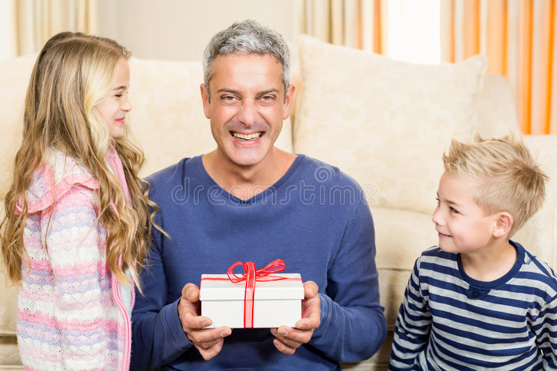 Happy father holding gift given by children. On the sofa stock image