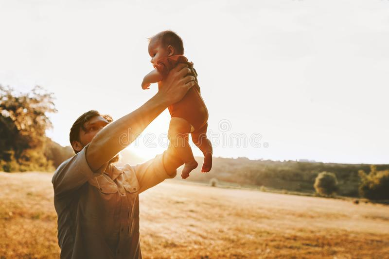 Happy father holding up infant baby outdoor Fathers day holiday royalty free stock images