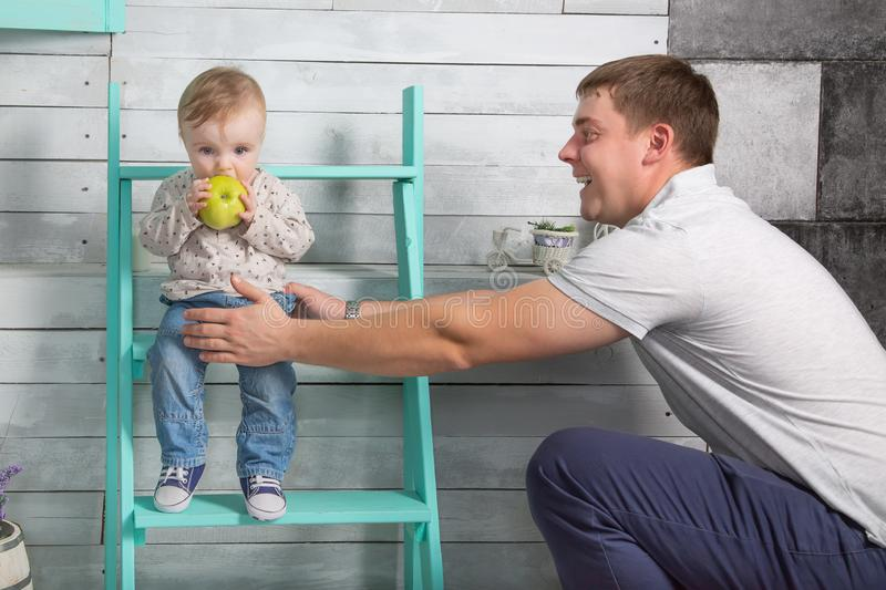 Happy father holds baby boy who eat big green apple. He both are in jeans and white hoodie.  Dad with son sits on the steps indoor. White wooden background royalty free stock photography