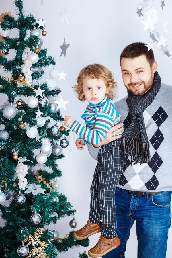 Happy father holds son near Christmas tree to decorate in white interior stock photo