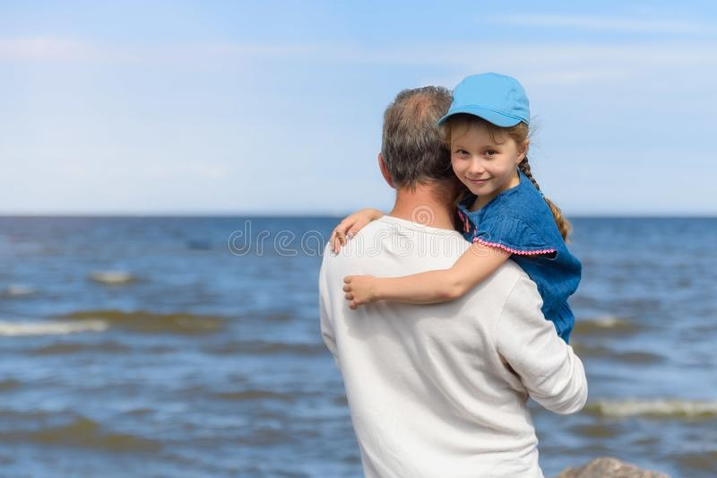 Happy father hugging his little daughter on the beach, father and daughter walking on the beach and posing to camera royalty free stock photography