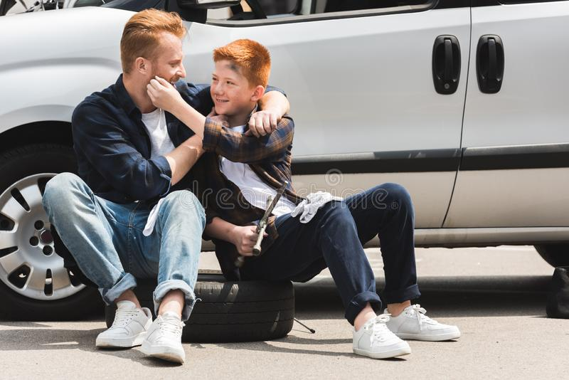 Happy father hugging son after repairing car and they. Having fun stock photo