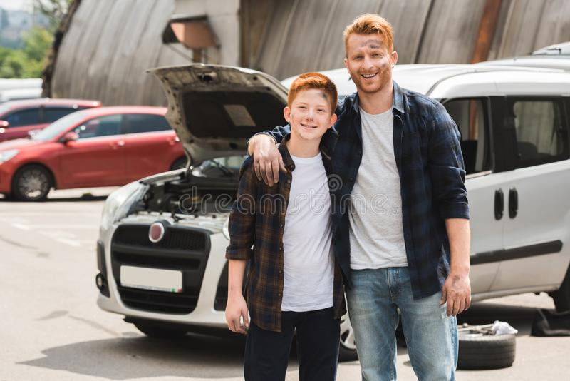 Happy father hugging son after repairing car and they looking. At camera royalty free stock photos
