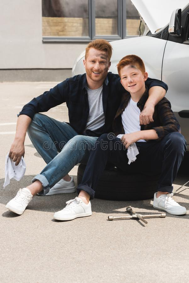 Happy father hugging son after repairing car and they sitting. Near auto stock image