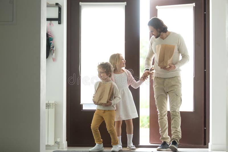 Smiling father with kids coming back home holding paper bags. Happy father with kids coming back home holding paper bag, little son helping dad to carry packets stock photos