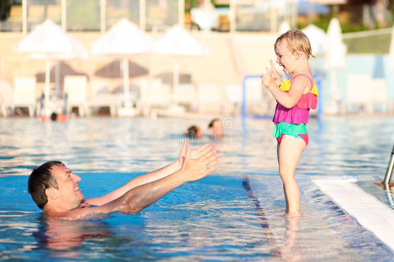 Happy father with little daughter in swimming pool stock photos