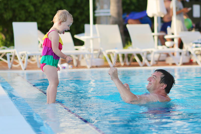 Happy father with little daughter in swimming pool. Happy family, active father with little child, adorable toddler girl, having fun together in outdoors royalty free stock photo