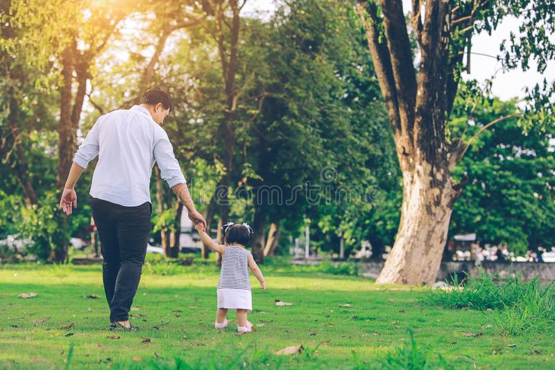 Happy father and little girl walking in summer park. adoption an stock photos