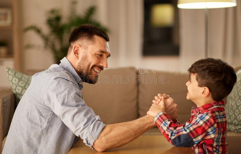 Happy father and little son arm wrestling at home. Family, fatherhood and people concept - happy smiling father and little son arm wrestling at home in evening royalty free stock images