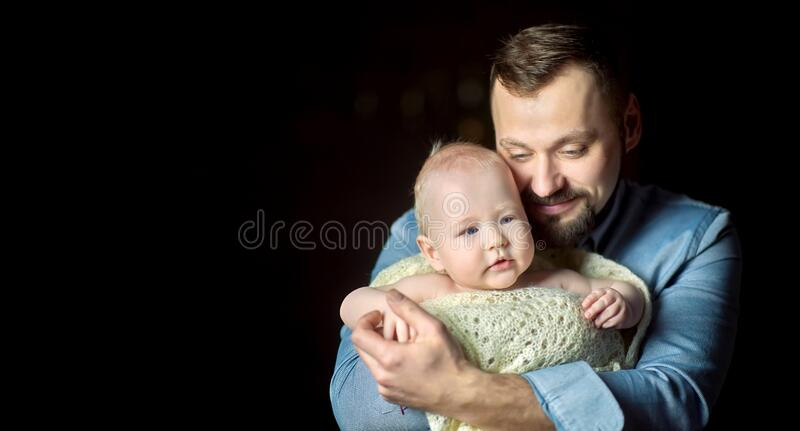 Happy father lives in the arms of a newborn baby. A happy father lives in the arms of a newborn baby, hugs and poses creamly. Paternity stock photo