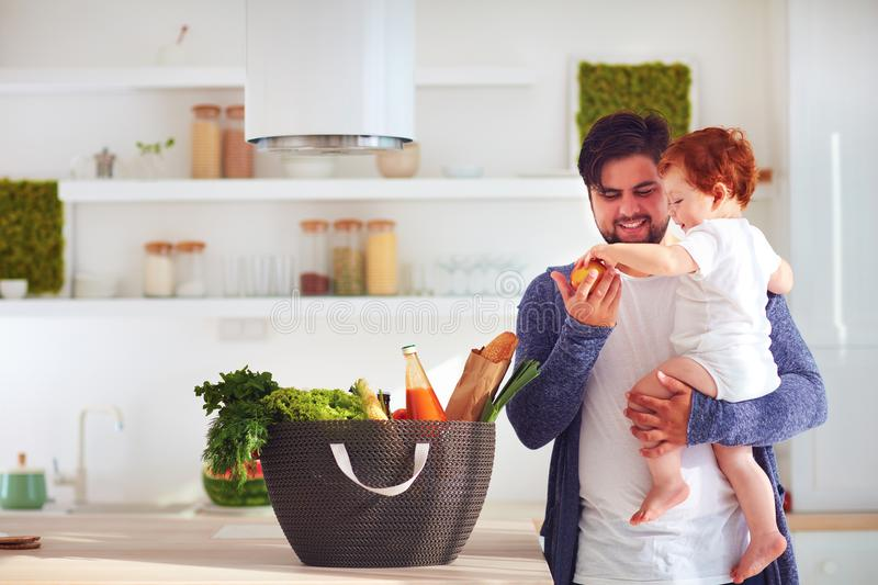 Happy father offering to infant baby son a fresh fruit from shopping basket, home kitchen stock images