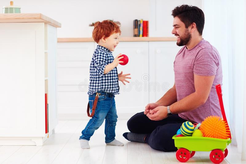 Happy father playing with cute toddler baby son at home, family games royalty free stock photos
