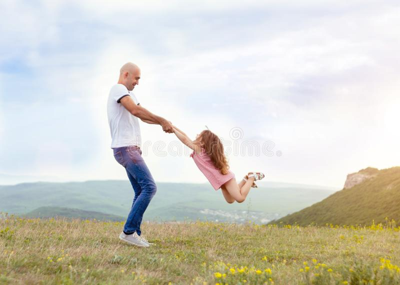 Father playing with his daughter in sunny field stock photo