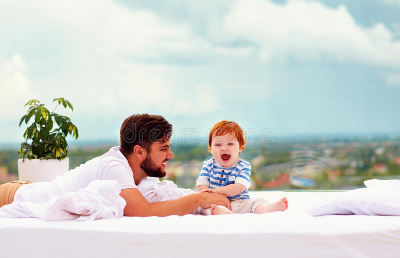 Happy father playing with infant son in bed in front of the window royalty free stock photo