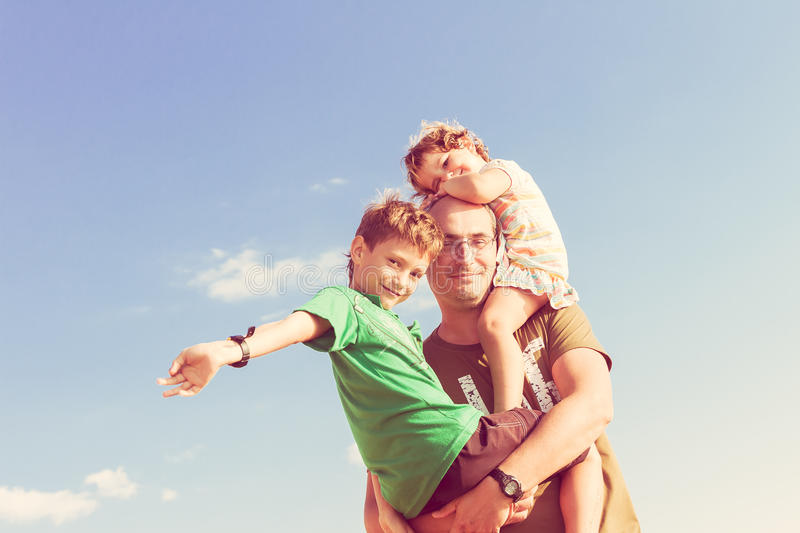 Happy father playing with kids outdoors. Happy father playing with two kids outdoors royalty free stock images