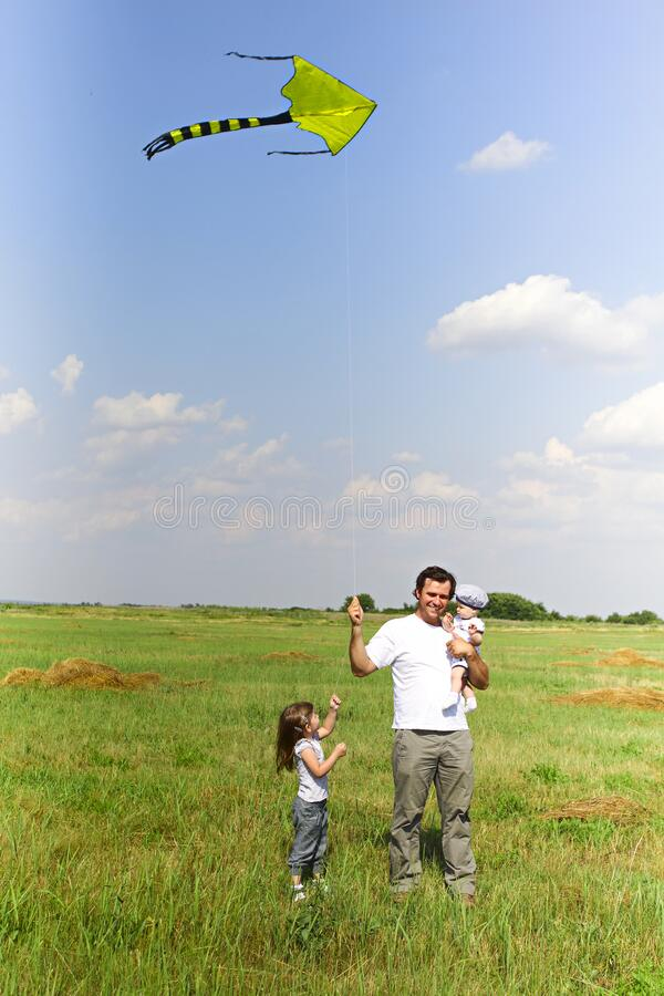 Happy father playing kite with children in meadow in sunny summer day. Happy man carrying infant baby and with small girl near holding flying kite while standing stock photo