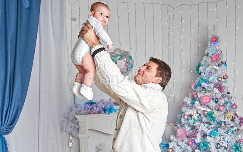 Happy father playing with little son near Christmas tree . royalty free stock photo