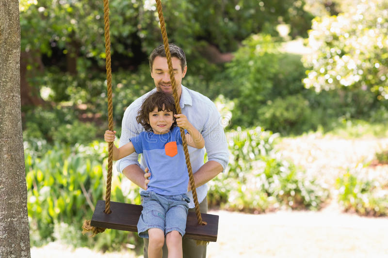 Happy father pushing boy on swing royalty free stock photos