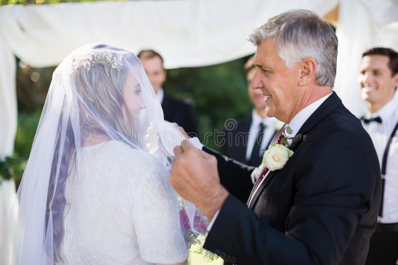 Happy father removing veil of his daughter stock photo