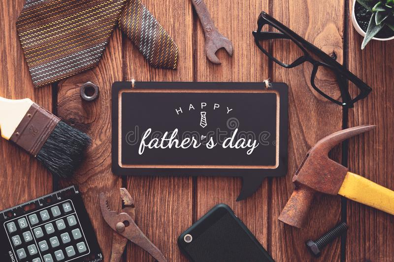Happy father`s day background concept. Flat lay of construction  handy tools and  gentleman`s accessories over wooden background. With black chalkboard and stock photos