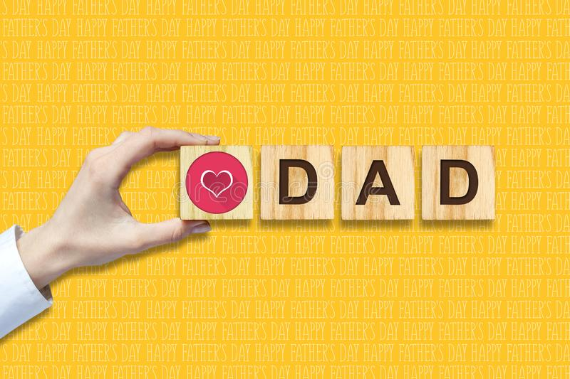 Happy father`s day background. Female hand with social heart icon. Yellow background. Congratulatory background stock images