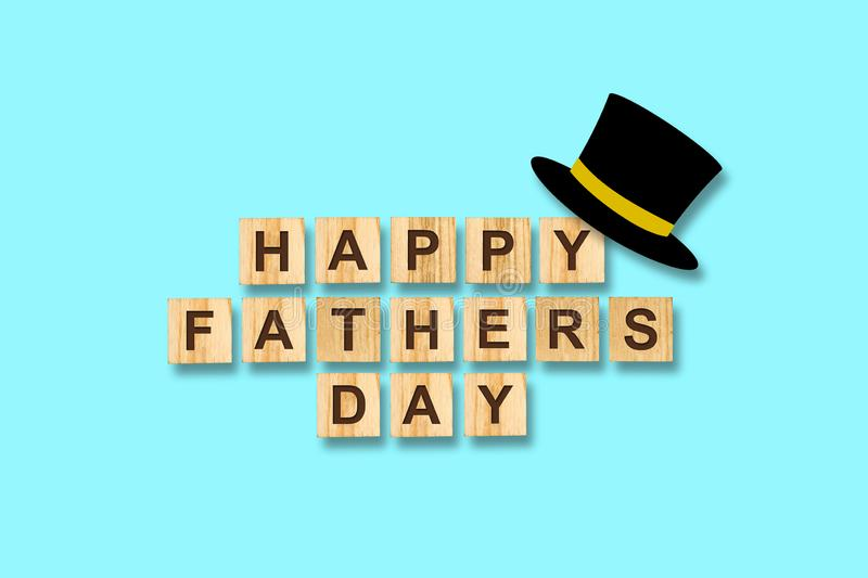 Happy father`s day background. Hat cylinder and the inscription on wooden blocks on a blue background. Congratulatory background royalty free stock photo