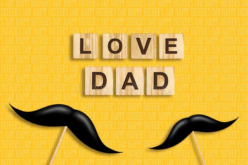 Happy father`s day background. Mustache on a stick. Love Dad, inscription on wooden blocks on a yellow background. Congratulatory stock illustration
