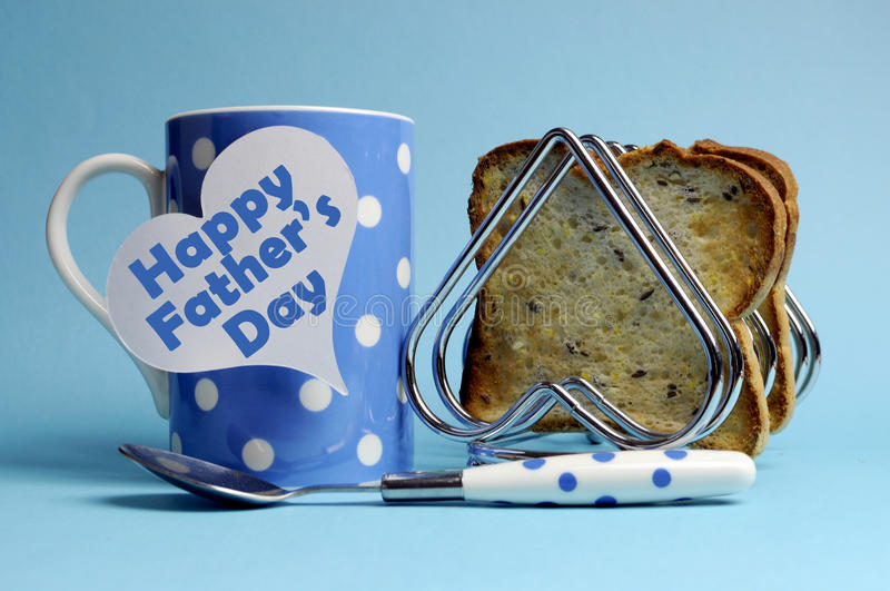Happy Father's Day breakfast. Message on white heart tag with polka dot coffee mug and heart rack with wholemeal toast on blue background stock photos
