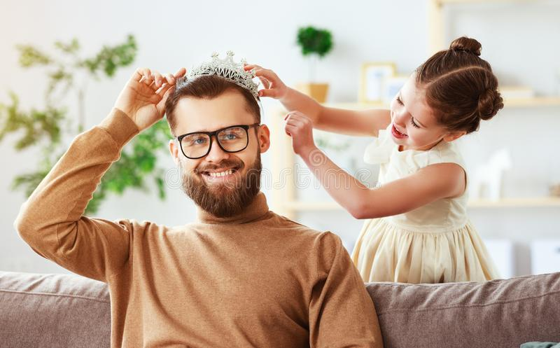 Happy father`s day! child daughter in crown does makeup to daddy. And laughs royalty free stock image