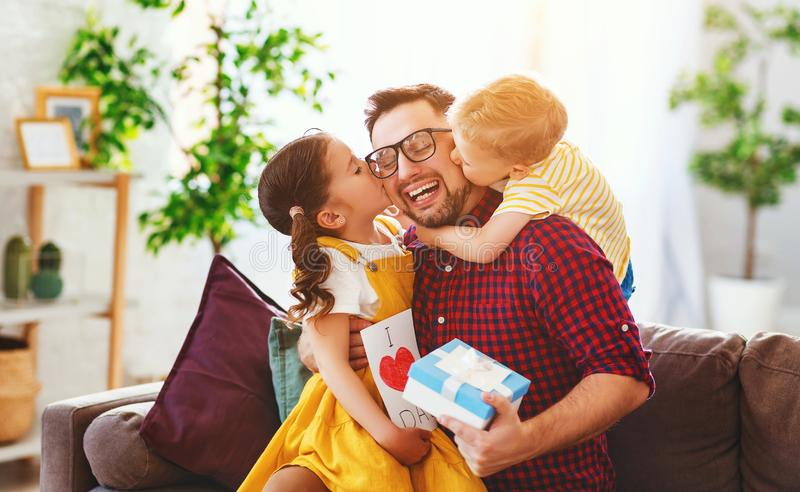 Happy father`s day! Children congratulates dad and gives him gift and postcard. Happy father`s day! Children congratulates dad and gives  him a gift and postcard stock photos