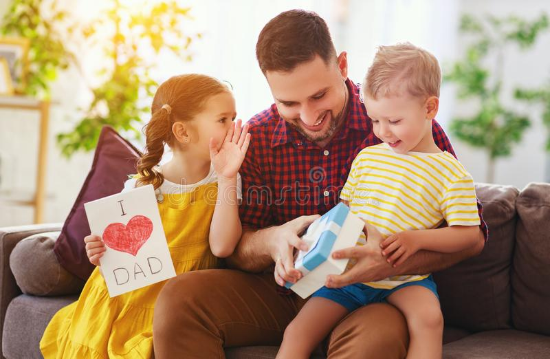 Happy father`s day! Children congratulates dad and gives him gift and postcard. Happy father`s day! Children congratulates dad and gives  him a gift and postcard stock image