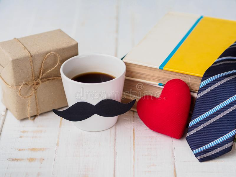 Happy father`s day concept. Gift box, a cup of coffee with musta stock images