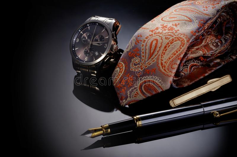 Happy Father& x27;s Day concept image with business man& x27;s watch, pen and tie folded against black gradient. Copy space. Happy Father& x27;s Day concept stock photo