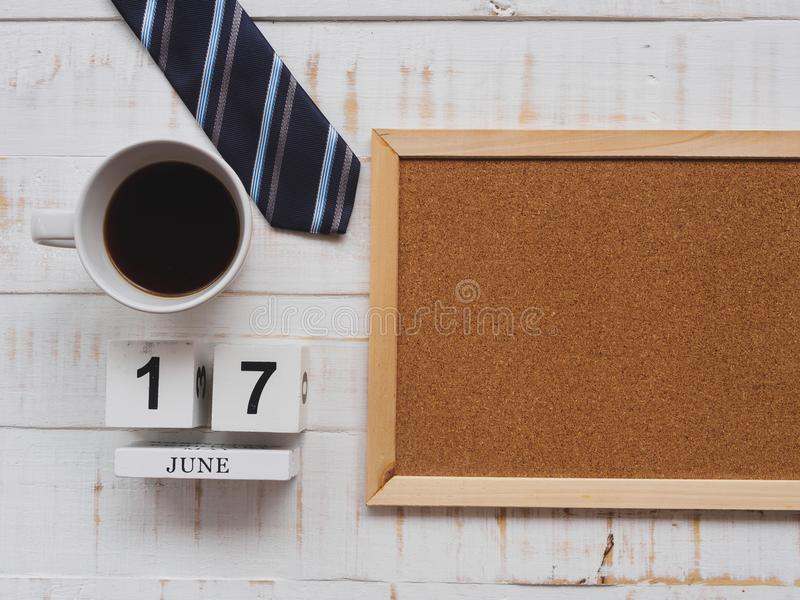 Happy father`s day concept. 17 June wooden block calendar, tie,. Board and a cup of coffee on white wooden background