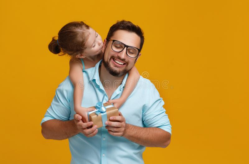 Happy father`s day! cute dad and daughter hugging on yellow back stock photo