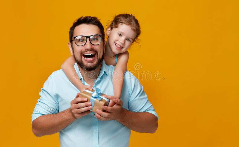 Happy father`s day! cute dad and daughter hugging on yellow back stock photos