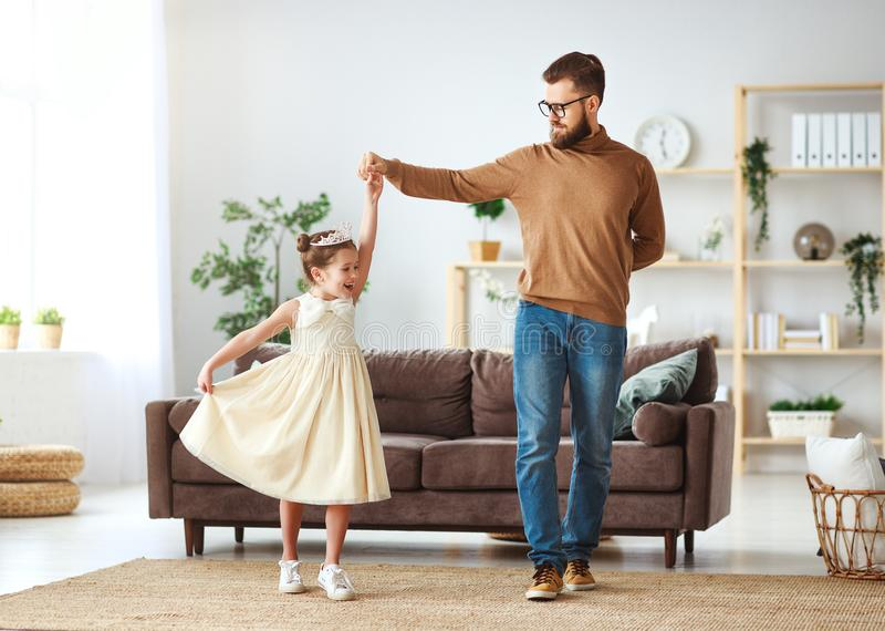 Happy father`s day! family dad and child daughter Princess dancing. At home royalty free stock image