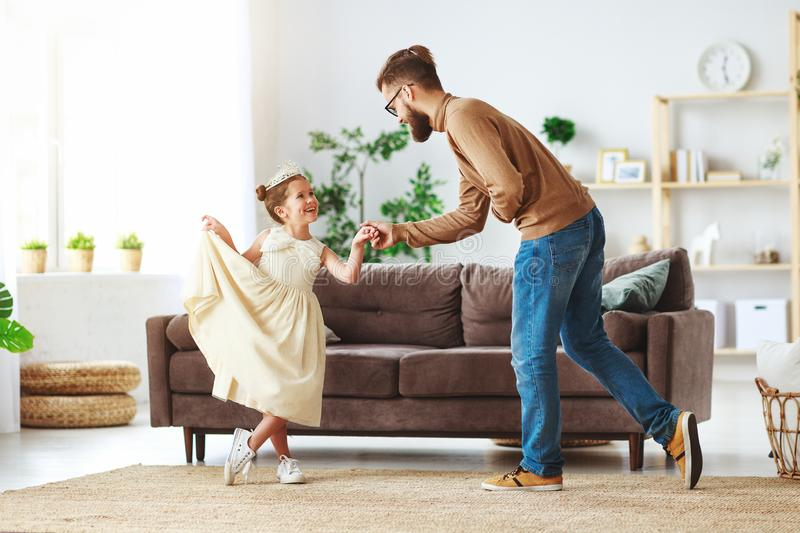 Happy father`s day! family dad and child daughter Princess dancing. At home stock image